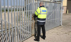 An Intacept Security Officer checks a gate while on foot patrol